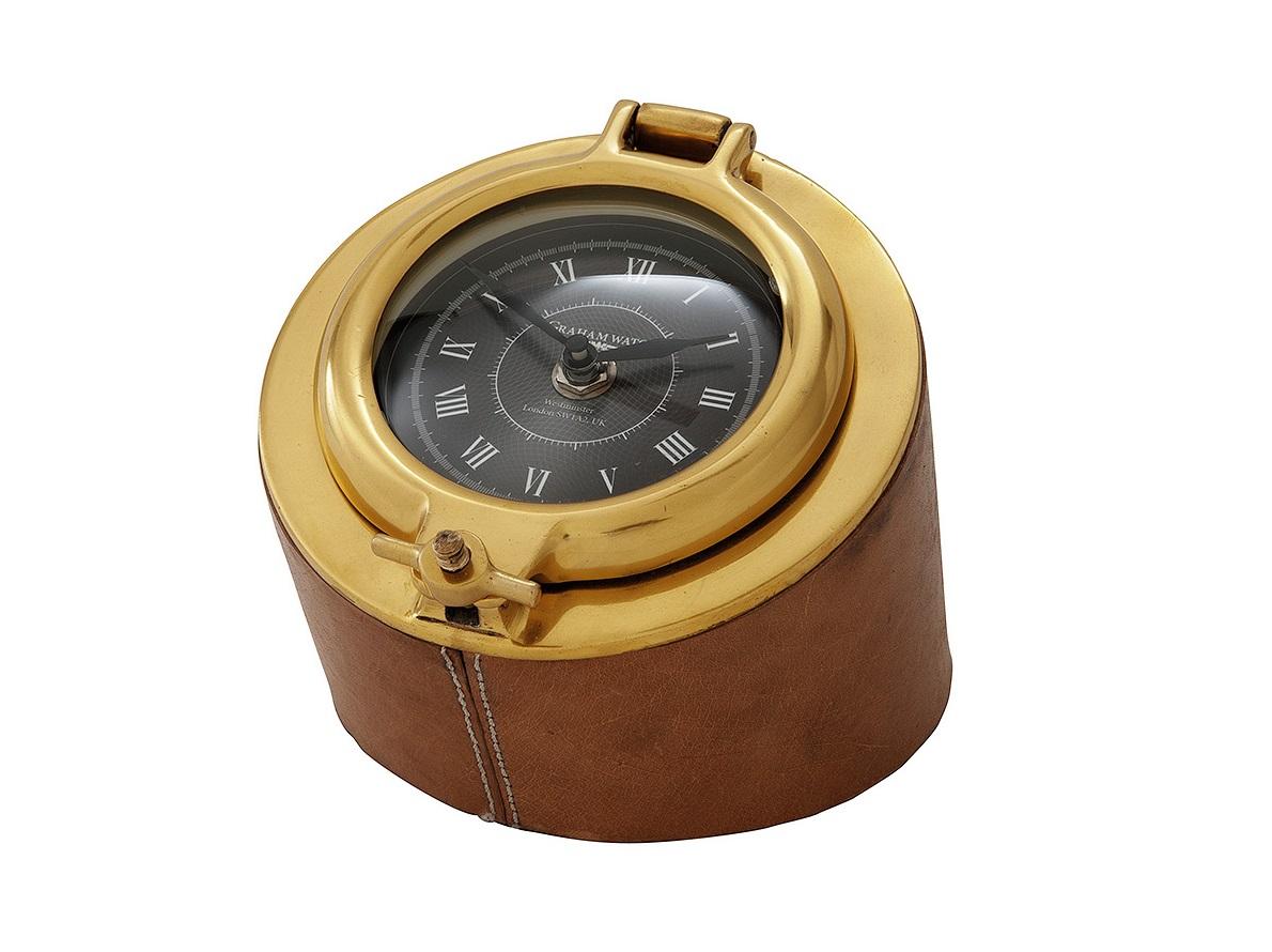 ЧасыНастольные часы<br>Настольные часы Graham. Комбинированное основание из металла цвета латунь и кожи коричневого цвета. Открывающаяся стеклянная крышка. Кварцевый механизм.<br><br>Material: Кожа<br>Width см: 14<br>Depth см: 14<br>Height см: 15
