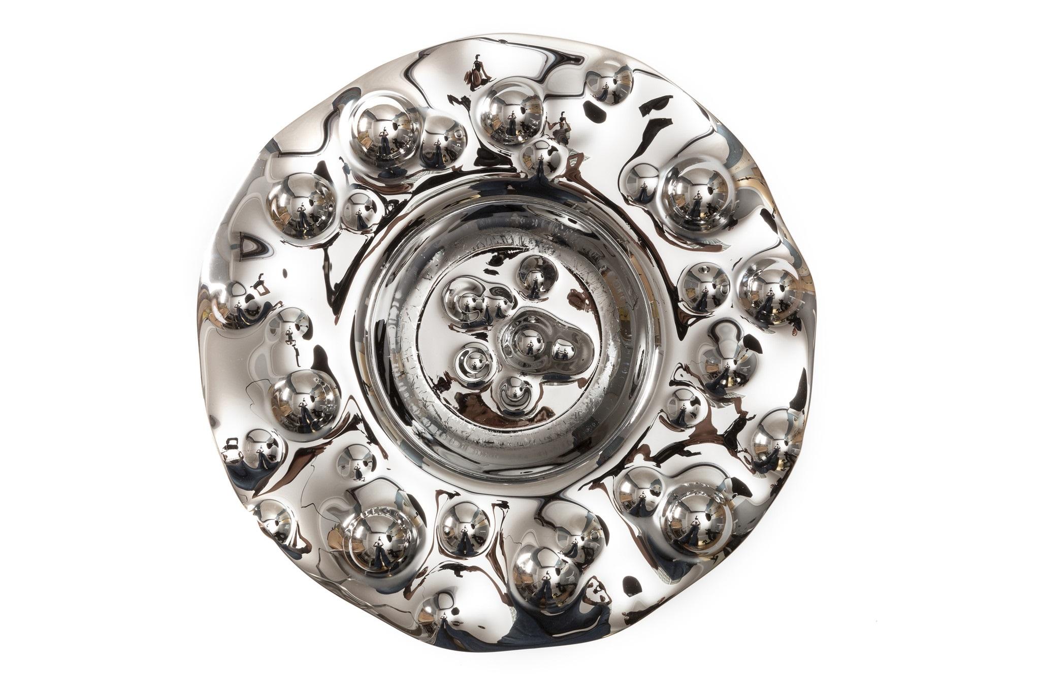 Ваза GeyzerДекоративные блюда<br>Как бурлящий фонтан, словно подземный горячий источник, Geyser Silver взрывает сознание, погружая в пучину собственных размышлений. Ценители практичных и компактных форм достойно оценят яркий и одновременно многофункциональный предмет интерьера под названием Geyser. Как уникальный арт-объект, в качестве вазы для фруктов, орешков и других вкусностей – найдите сами лучшее применение этому изделию.<br><br>Material: Стекло<br>Height см: 12<br>Diameter см: 41