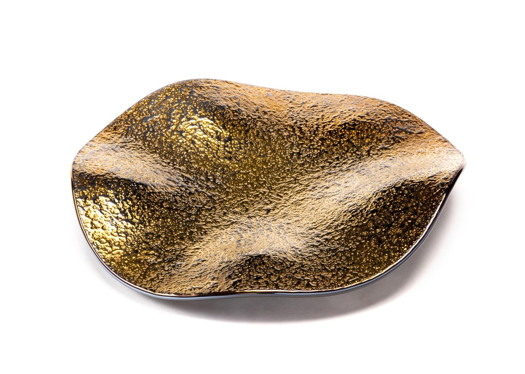 Ваза StingrayДекоративные блюда<br>Тот кто один раз видел Stingray Golden Galaxy, постигнет любовь с первого взгляда. Ваза завораживает, от нее невозможно отвести глаз. Stingray становится настоящим центром интерьера, но при этом она может отлично вписаться в уже установленные интерьерные рамки пространства. Stingray Golden Galaxy - это и эффектная ваза, и завораживающий поднос, а также великолепная тарелка для сервировки обеденного стола.<br><br>Material: Стекло<br>Высота см: 10