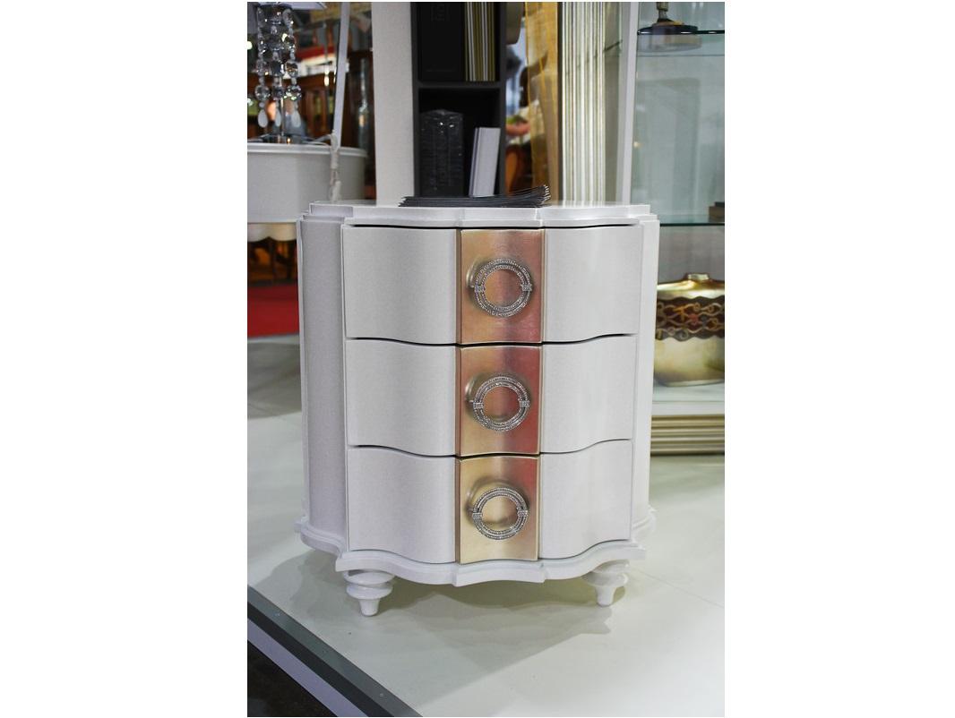 Прикроватная тумба RiminiПрикроватные тумбы<br>Отделка белый матовый лак. Центральная часть фасада в отделке сусальное серебро. Ручки украшены стразами. Оригинальность модели обусловлена закругленной формой и низкими фигурными ножками.&amp;amp;nbsp;&amp;lt;div&amp;gt;Сделана из высококачественного МДФ высокой плотности и массива дерева.&amp;amp;nbsp;&amp;lt;/div&amp;gt;&amp;lt;div&amp;gt;Все выдвижные ящики снабжены направляющими.&amp;lt;/div&amp;gt;<br><br>Material: Дерево<br>Width см: 63<br>Depth см: 63<br>Height см: 65