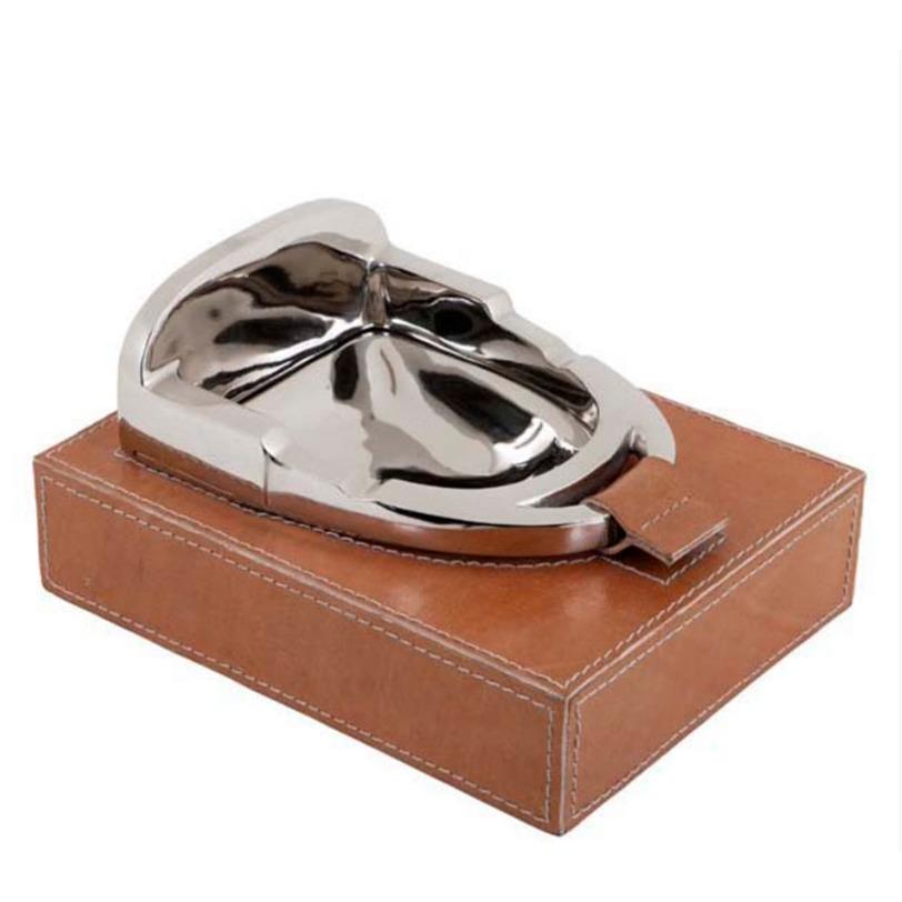 Пепельница Ashtray AscotДругое<br>Пепельница Ashtray Ascot с основанием в виде коробки покрытой коричневой кожей, украшена фигурой из металла цвета никель в виде стремяни.<br><br>Material: Металл<br>Length см: 21<br>Width см: 16<br>Depth см: None<br>Height см: 11<br>Diameter см: None