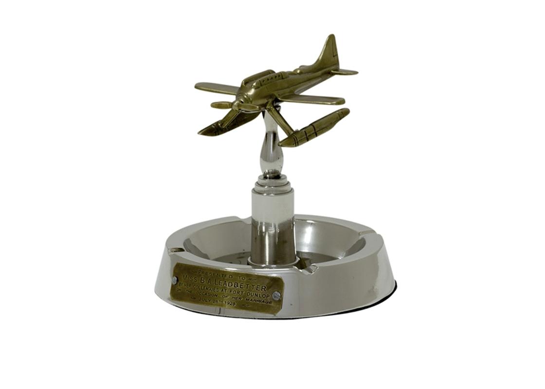 ПепельницаДругое<br>Пепельница с оригинальным дизайном в виде летящего самолетика из коллекции Dakota выполнена из металла стального цвета. Цвет самолета - бронзовый.<br><br>Material: Металл<br>Height см: 20<br>Diameter см: 16.5